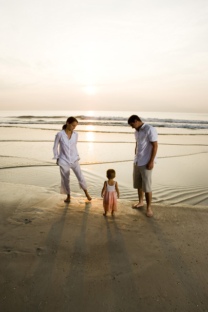 Young couple with daughter relaxing on the beach
